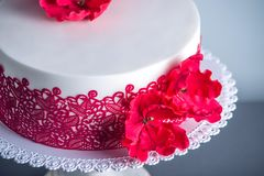 White wedding cake decorated with flowers sugar poppies and red pattern ornament. Concept of elegant holiday desserts. Beautiful white wedding cake decorated Royalty Free Stock Photos