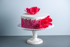 White wedding cake decorated with flowers sugar poppies and red pattern ornament. Concept of elegant holiday desserts. Beautiful white wedding cake decorated Stock Photo