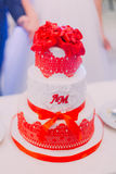 White wedding cake decorated with newlywed first letters, ribbons and red flowers on top Stock Images