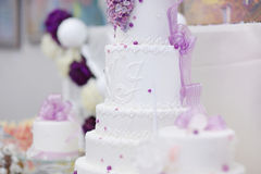 White wedding cake decorated with purple flowers Stock Photo