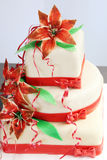 White wedding cake decorated with red decorations and sugar flowers - lilys Royalty Free Stock Images