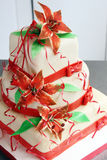 White wedding cake decorated with red decorations and sugar flowers - lilys Royalty Free Stock Photos