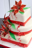 White wedding cake decorated with red decorations and sugar flowers - lilys Stock Image