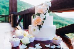 White wedding cake with flowers on a wooden table. royalty free stock photo
