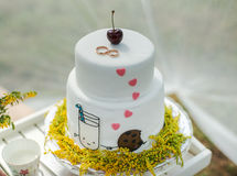White wedding cake with gold rings Royalty Free Stock Image