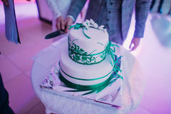 The white wedding cake with green ribbons placed on the table. Royalty Free Stock Photos