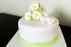 White wedding cake from the mastic with chamomile decor stock photography