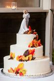White wedding cake with orange and brown fondant icing fall colored leaves and a bride and groom on top royalty free stock photos