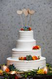 White wedding cake with orange and yellow fondant icing flowers and a succulent plant with three blank wooden bird and heart. Shaped toppers - wedding cake royalty free stock images