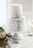 White wedding cake with silver decoration. And wedding bouquet with ranunculus Stock Image