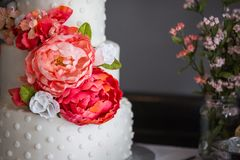A beautiful three tiered wedding cake with flowers royalty free stock image