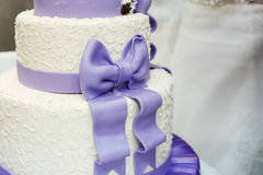 White wedding cake and violet bow Royalty Free Stock Images