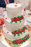 White wedding cake on wedding banquet with red rose and other flowers Stock Photography