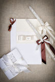 White wedding card with ribbon and paper lace. Candles with ribbons Royalty Free Stock Images