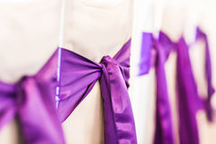 White wedding chairs decorated with purple bows Stock Photos
