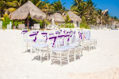 White wedding chairs decorated with purple bows on Royalty Free Stock Photo