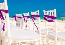 White wedding chairs decorated with purple bows on Royalty Free Stock Photos