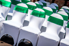 White wedding chairs. With green ribbon outdoors Royalty Free Stock Photography