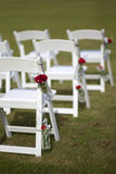 White wedding chairs. With rose ornaments hanging on side Royalty Free Stock Photography