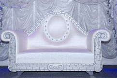 White wedding chic sofa on the stage on the background of white curtains Royalty Free Stock Images