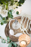 White wedding decor, perfume, pearl beads and bouquet of flowers Royalty Free Stock Photography