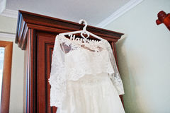 White wedding dress of bride on hangers at closet. Stock Image
