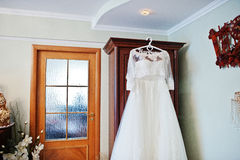 White wedding dress of bride on hangers at closet. Royalty Free Stock Images