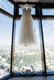 White wedding dress hanging in the bedroom. White bride dress royalty free stock image