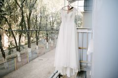 White wedding dress hanging in the bedroom. White bride dress stock photography