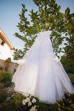 White wedding dress hanging in a garden Royalty Free Stock Images
