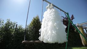 White wedding dress hanging on a green swing in the garden. Wedding dress on a tree bride, beautiful, female, beauty, fashion, white background cute stock video footage