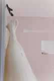 White wedding dress hanging on a shoulders Stock Image