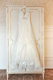 White Wedding dress. Hanging on a shoulders. Soft light and colours Royalty Free Stock Image