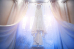 White Wedding dress hanging in a window. Royalty Free Stock Image
