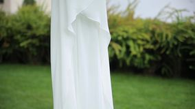 White wedding dress hangs on clothes for hanger. Close up. White wedding dress hangs on clothes for  hanger on green tree, under the hanging dress is the lawn stock video