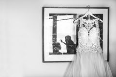 White wedding dress hangs on hanger in room while the bride is doing a makeup silhouette. White wedding dress hangs on hanger in room wall while the bride is Stock Image