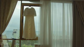 White wedding dress hangs in the window before the ceremony stock footage