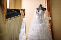 White wedding dress with ruffles and open shoulders on a mannequin stock images