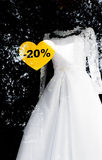 White wedding dress with sale sign of a discount in the window Royalty Free Stock Photography