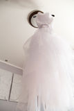 White wedding dress weighs on lamp in room. Royalty Free Stock Photography