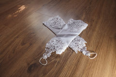 White wedding gloves lying on the wooden floor Royalty Free Stock Photography