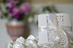 White wedding invitation, blurred background with purple orchids Royalty Free Stock Images