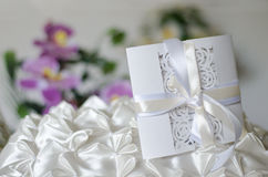 White wedding invitation on a satin pillow Royalty Free Stock Photography