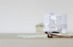 White wedding invitation on the texture background, candles decorated with ribbons Royalty Free Stock Image