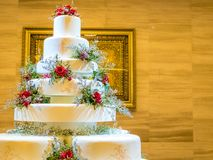 White wedding large cake with flowers decoration. In the room lighting Royalty Free Stock Images