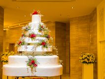 White wedding large cake with flowers decoration. In the room lighting Stock Photos