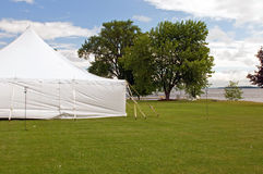 White wedding party tent. A large white wedding party tent on a grassy lawn at a lakeside resort Royalty Free Stock Photography