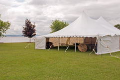 White wedding party tent. A large white wedding party tent on a grassy lawn at a lakeside resort Stock Photos