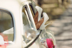 White Wedding Shoes. Bride's feet in white wedding shoes in car window Royalty Free Stock Images