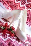 White wedding shoes on a embroidery ukrainian background. Royalty Free Stock Photo